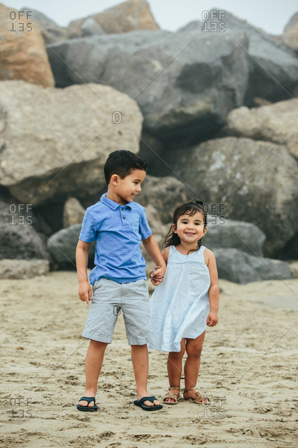 Young Brother Holds Toddler Sister's Hand At Beach
