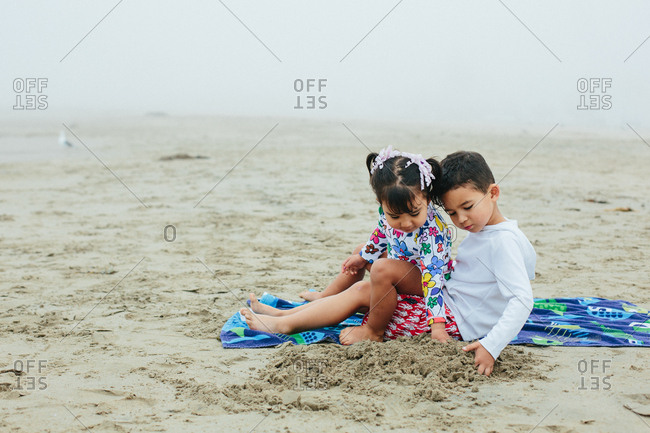 Toddler Girl Sitting On Brother's Lap While Playing with Sand At Beach