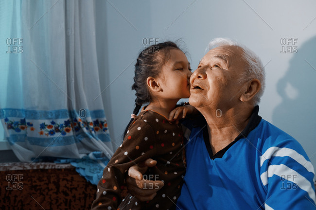 Little girl kissing her grandfather
