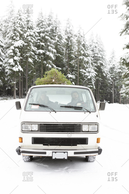 Man and woman driving van on snow covered road with Christmas tree