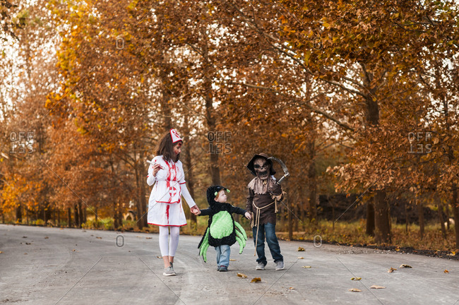 Siblings dressed up in their halloween costumes walking on fall trail