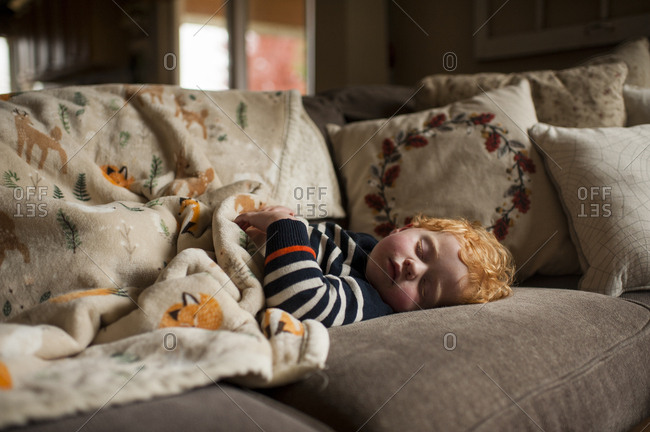 young boy sleeping on couch at home under warm blanket