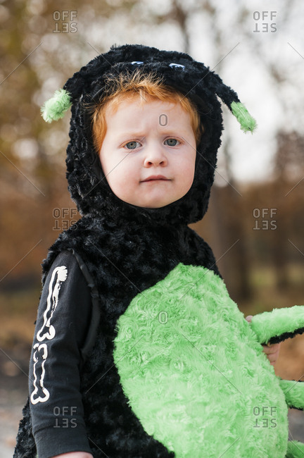 little boy dressed up as cute spider for halloween outdoors