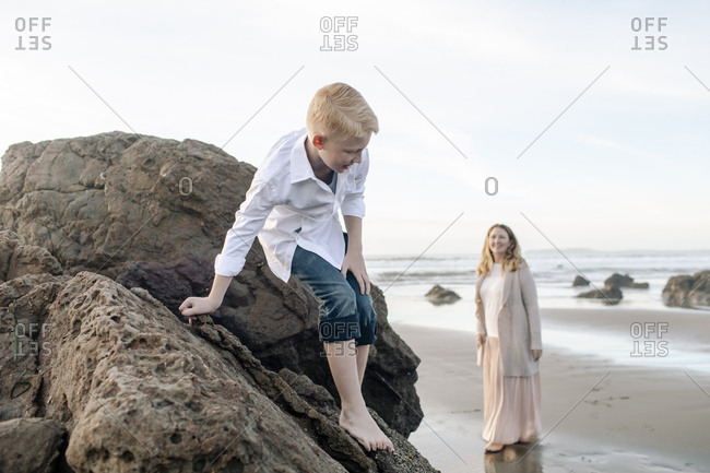 Mom watching  son climbs down the rock at the beach
