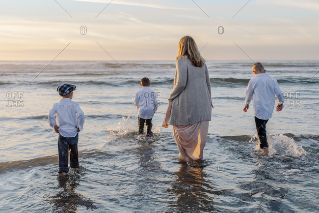 Rear view of Mom and her boys playing in the waves during sunset