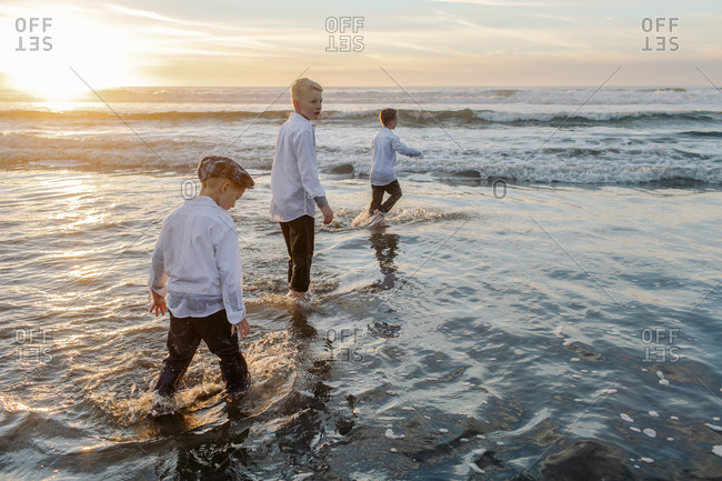 Three kids running on the water by the beach