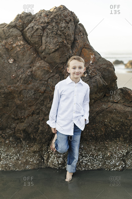 Portrait of a cute boy on the rock by the sea