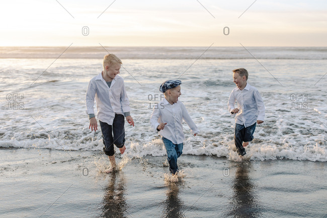 Front View of brothers running on the waves during sunset at beach