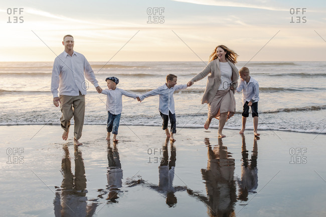 Happy family holding hands against sky during sunset at beach