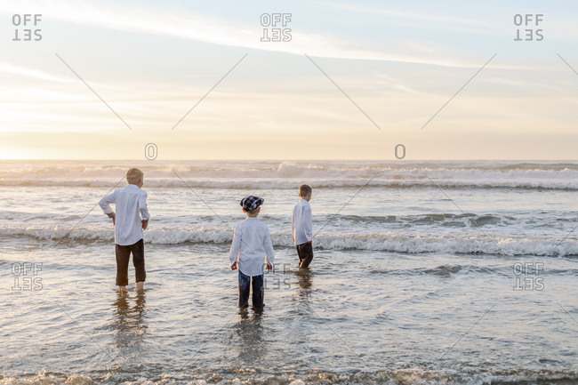 Rear view of the boys on the water by the beach