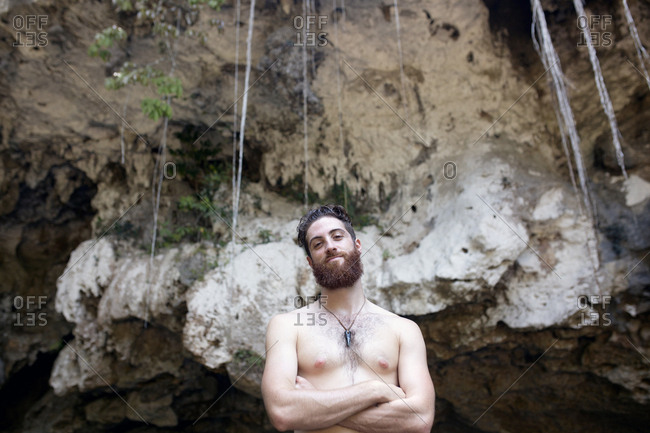 Man outside a cave with arms crossed
