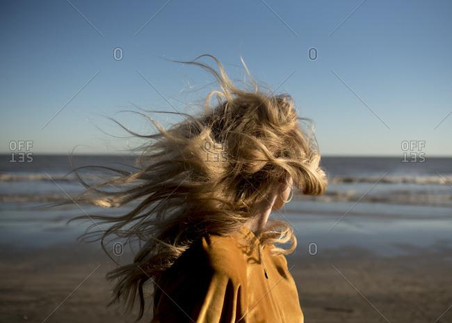 Women on the beach with windblown hair.