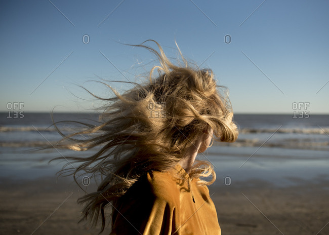 Women on the beach with windblown hair.