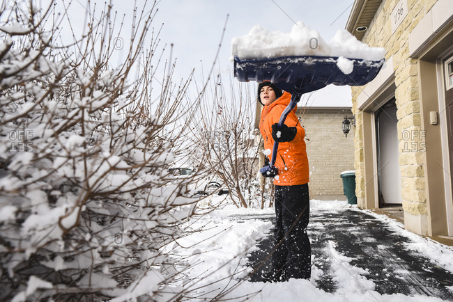 Boy shoveling snow off of a driveway after a winter storm