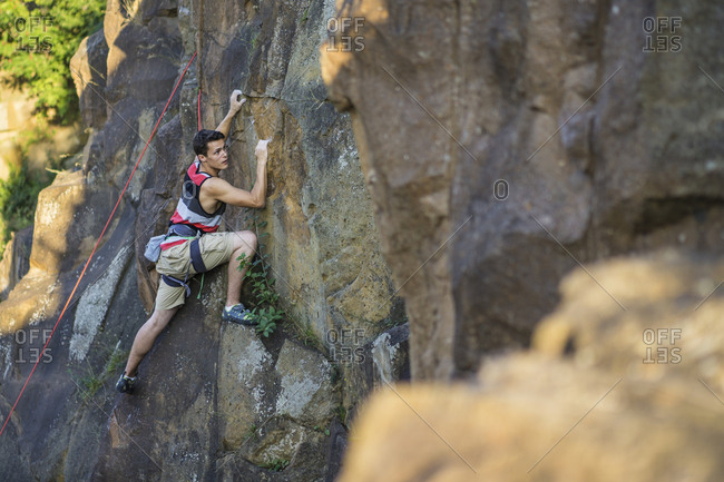 Rock climber on wall reaching forward