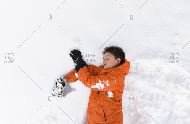 Tired boy with eyes closed laying on snow covered ground