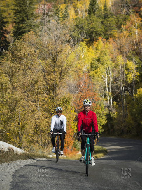 Happy couple riding bicycles on mountain road in autumn