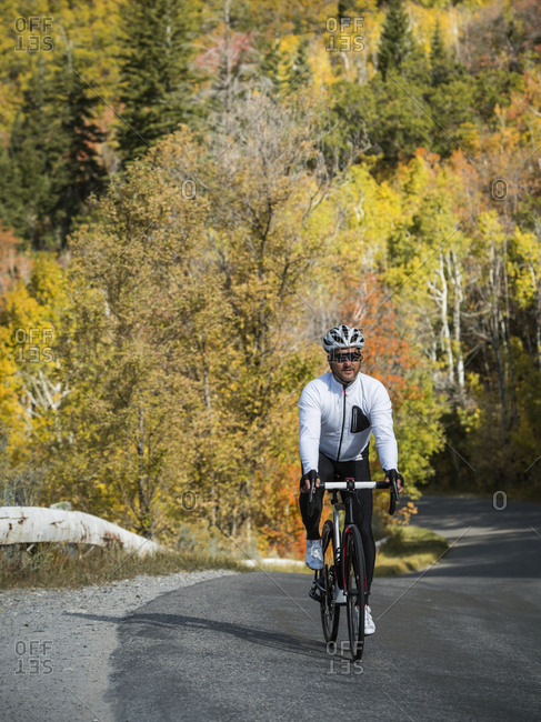 Healthy Caucasian man cycling along mountain road in autumn