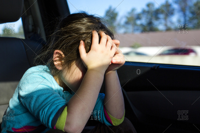 a small child impatiently sits in traffic, head in hands