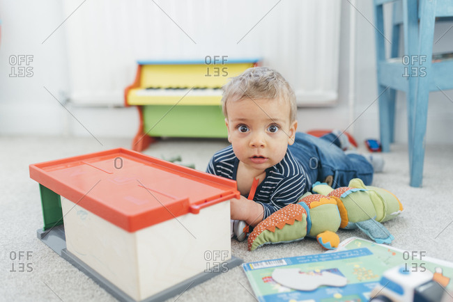 Baby boy crawling on carpet surrounded with toys
