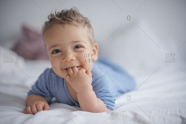 Smiling baby boy lays in bed with fingers in his mouth
