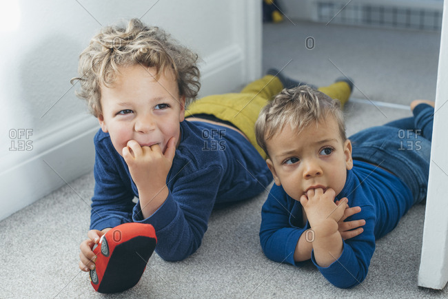 Young boy imitates baby brother sucking his fingers