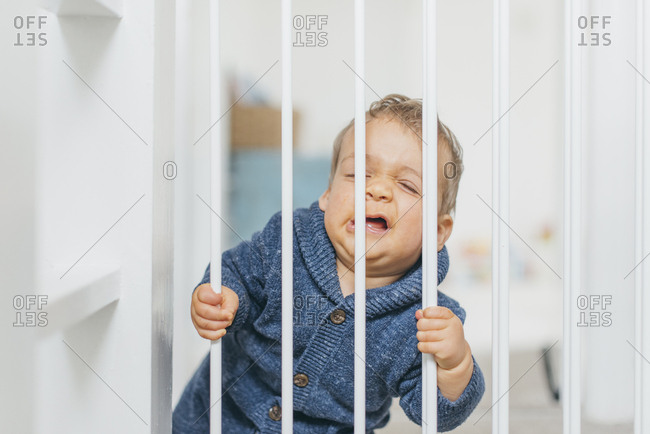 Baby boy squeezes his face on a baby gate