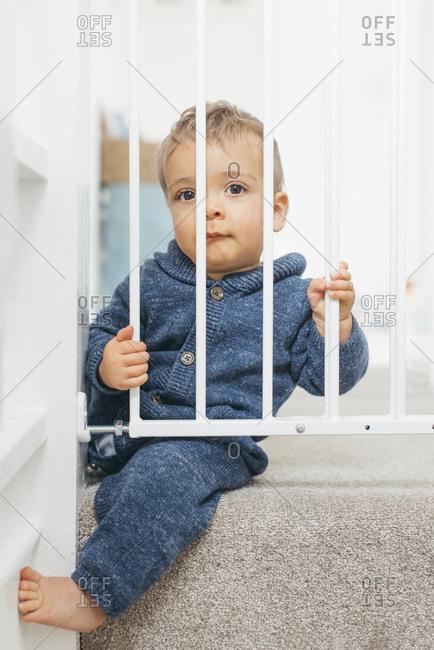 Baby boy sitting behind safety gate