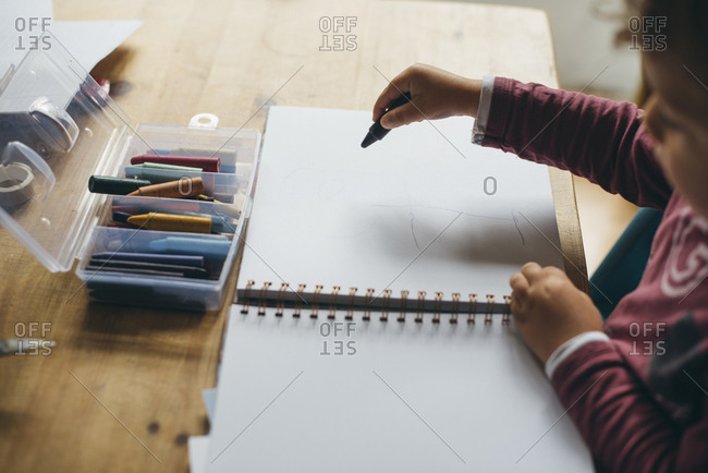 Child drawing on book while sitting at table