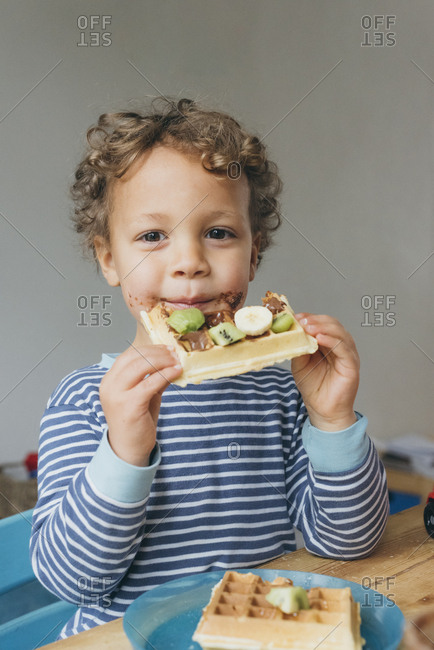 Boy eats a chocolate waffle at the table