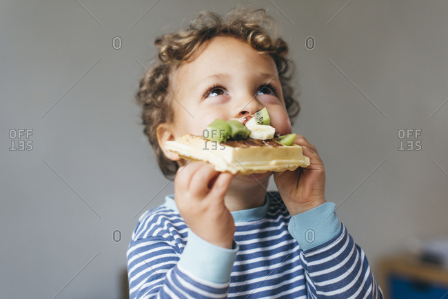 Young boy eating chocolate and fruit waffle