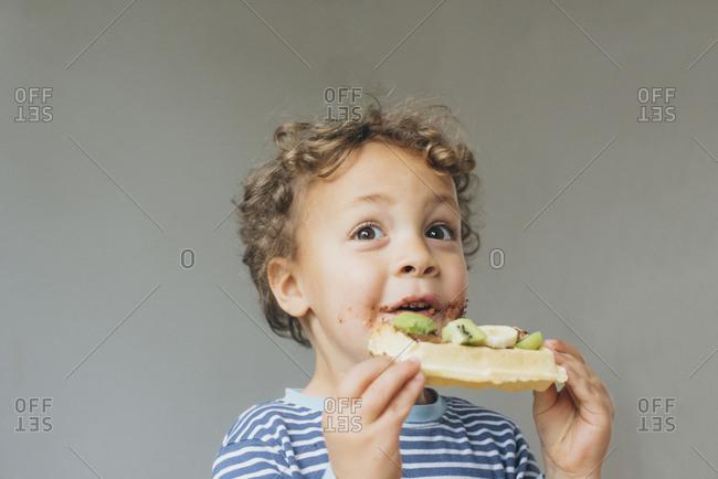 Cute little boy eats a waffle