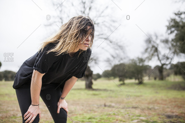 beautiful and young woman training running in the rain on the outskirts of the city