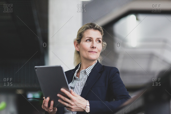 Senior female business executive using digital tablet in a corporate office
