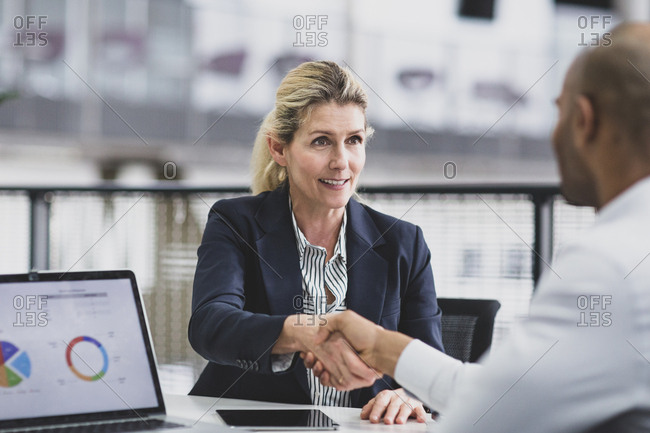 Senior female business executive shaking hands