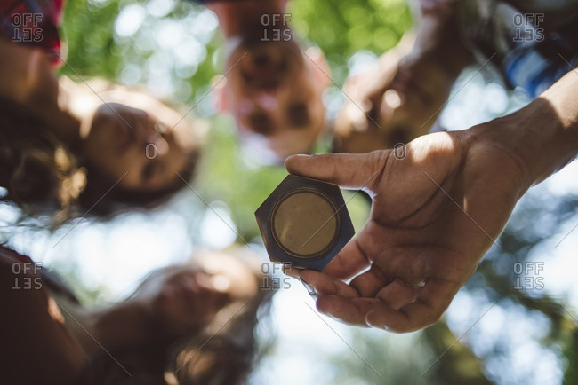 Group of friends looking an old compass in the forest