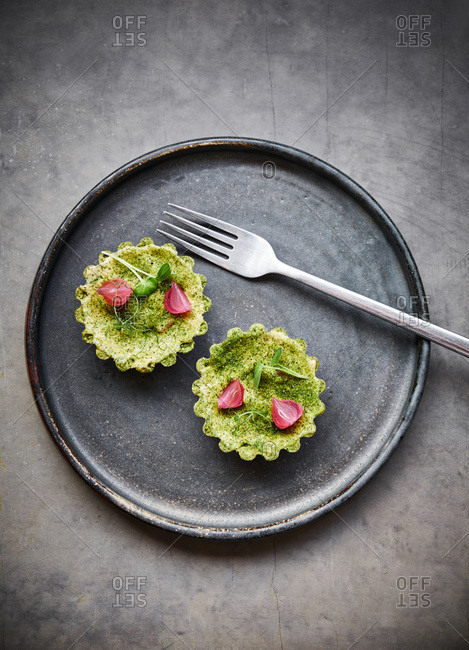 Two tartlets on a dark plate on gray background