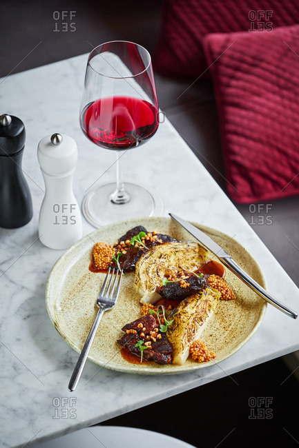 Gourmet pork cheek dish with baked celery root and French mustard served with wine