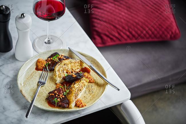 Gourmet pork cheek dish served with wine