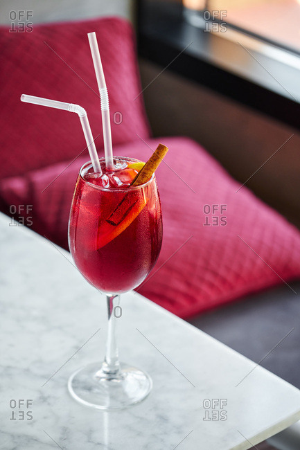 Red cocktail garnished with a cinnamon stick and lemon