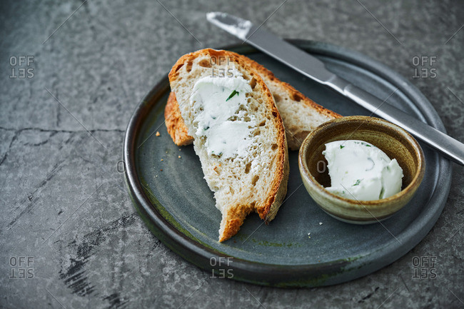 Slices of fresh bread with homemade goat cheese and herbs