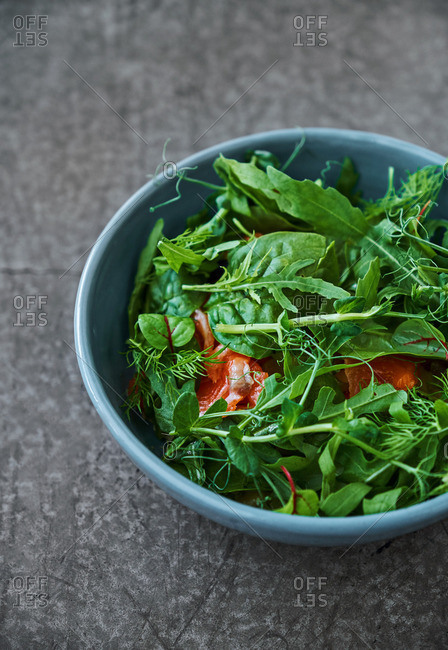 Close up of a salad of various greens and trout