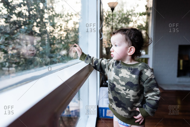 Baby boy looking out window and pointing