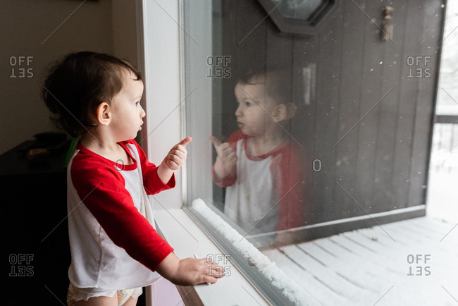Baby boy looking out window at snow and pointing
