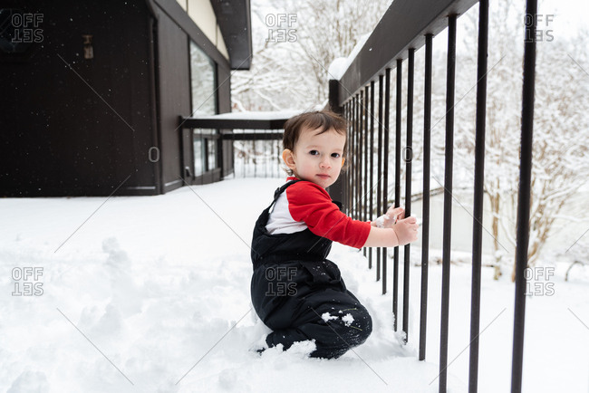 Toddler boy on a snowy deck