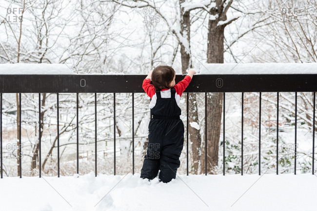 Toddler boy knocking snow off of railing
