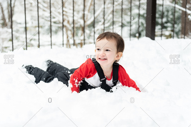 Toddler boy lying in the snow on a snowy deck