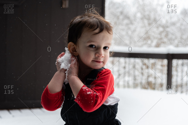 Toddler boy playing with snow on a snowy deck