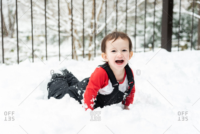 Happy toddler boy playing in the snow on a snowy deck
