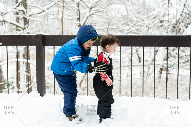 Two boys playing in the snow on a snowy deck